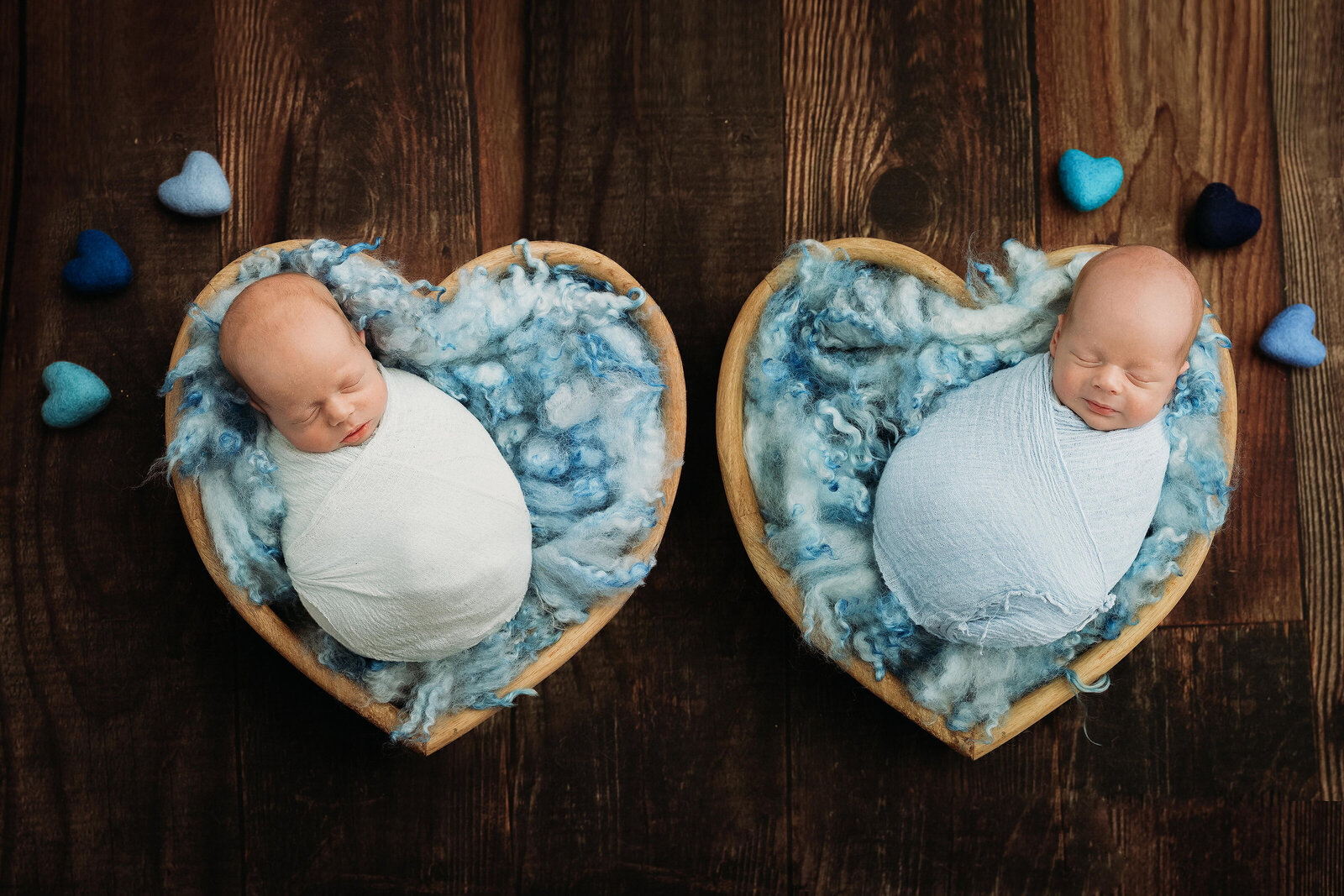 In-studio portrait of twin newborn babies posed in hearts on wood floor