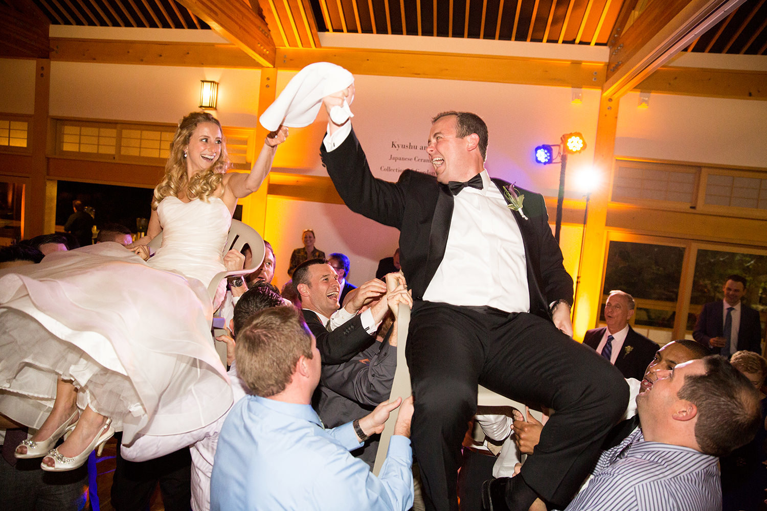 bride and groom lifted on chairs at the reception