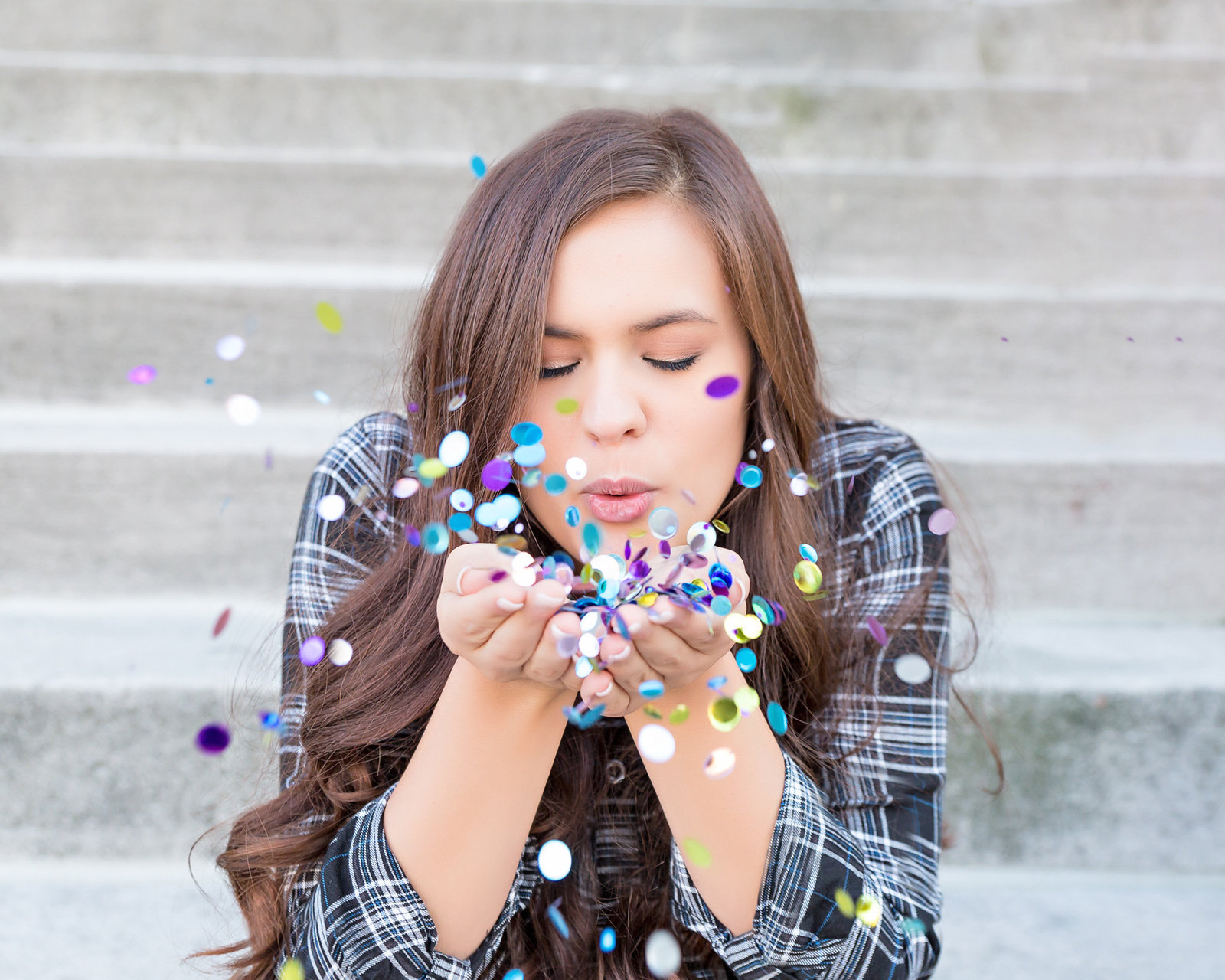 Senior girl on steps blowing confetti