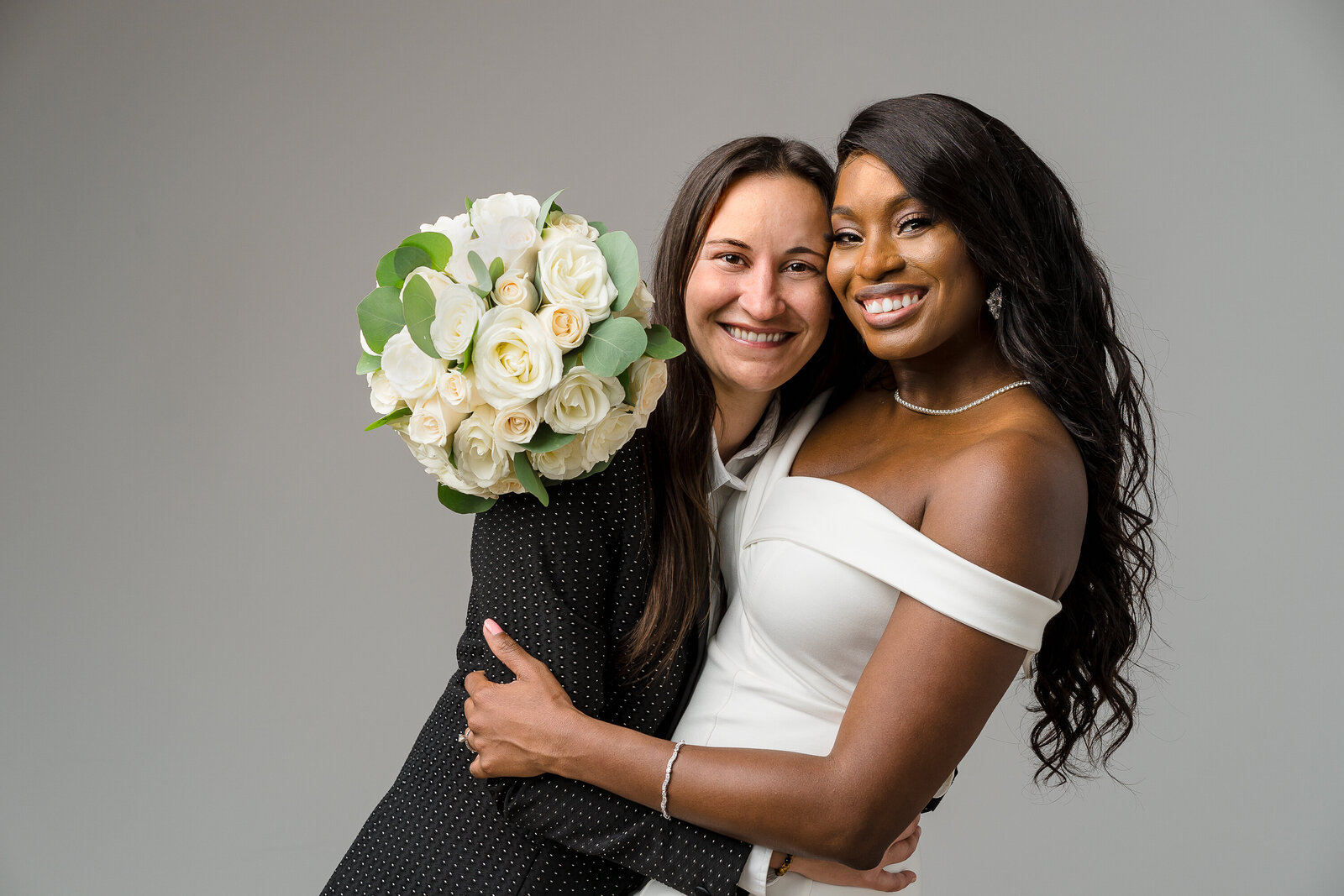 An interracial lesbian couple embrace in a studio portrait for their back yard wedding.