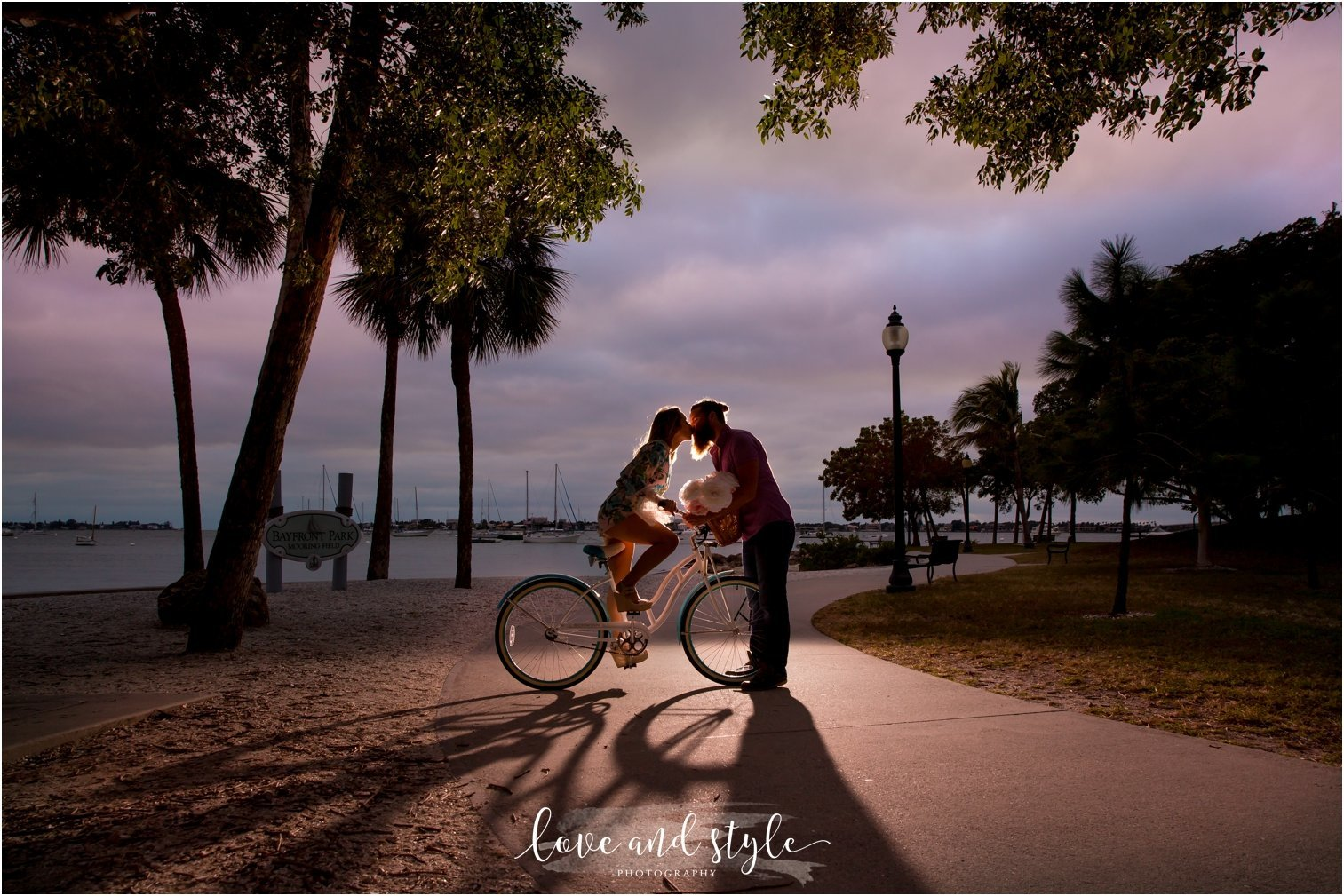 Sarasota Engagement Photography of couple kissing on a blue beach cruiser in Bayfront Park at sunset