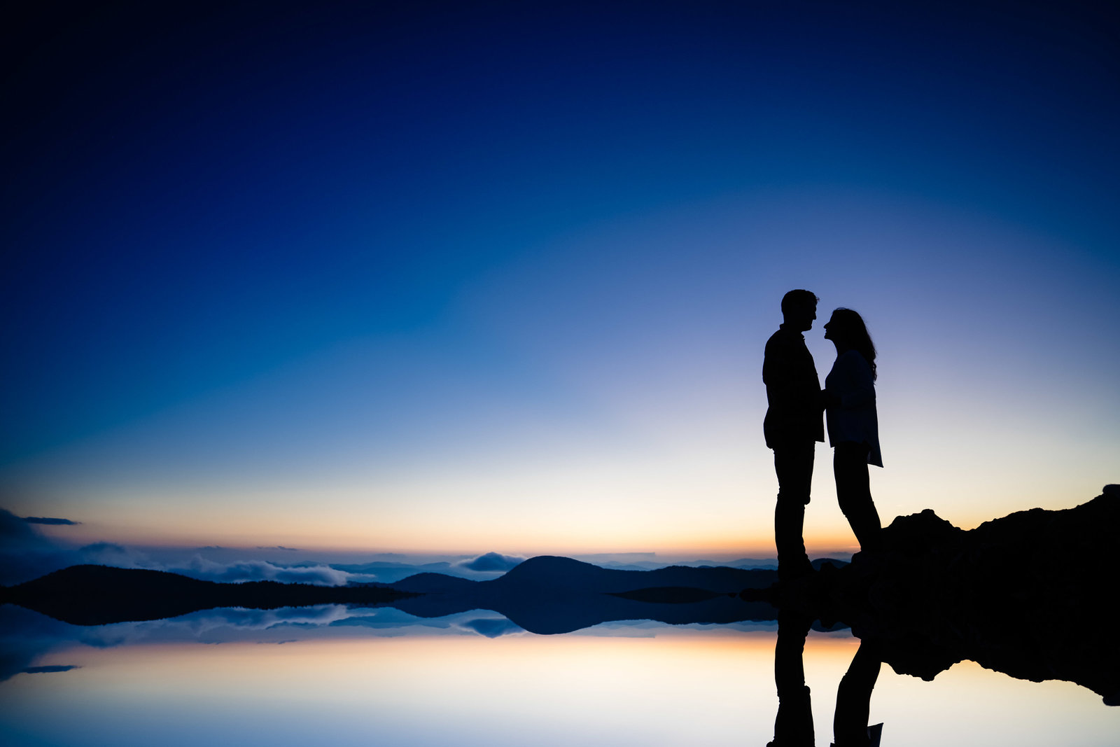 couple silhouette on top of mountain