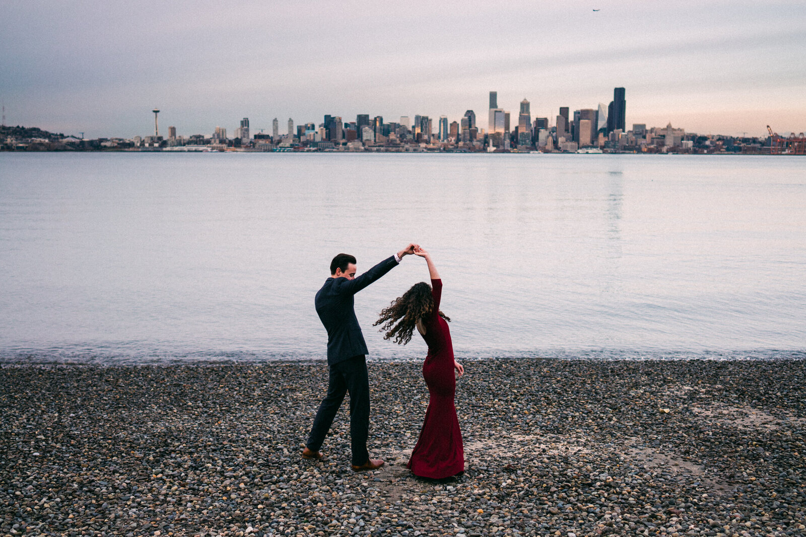 Engaged couple dancing along the Puget Sound beach for their engagement pictures with the skyline, one of the most creative engagement photos in Seattle