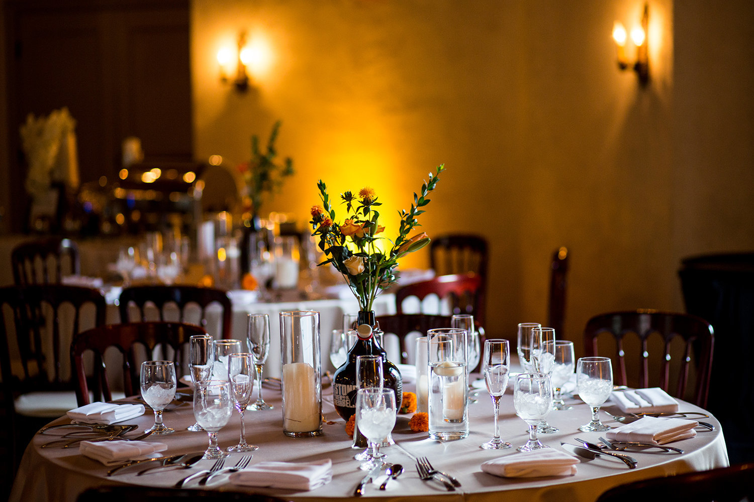 Warm amber uplighting set the perfect mood for this wedding table setting