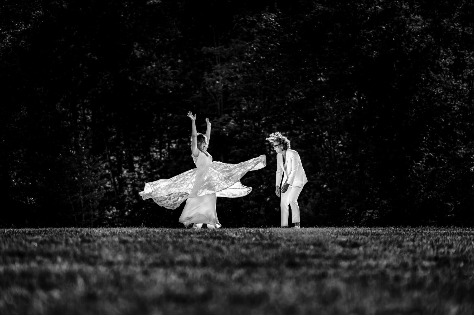 Two brides in a black and white photo dancing in an open field together. Hillary Stirling, NYC Chef flings her hair forward in laughter. Electric Love Studios is a  Lesbian owned business buy two wives.