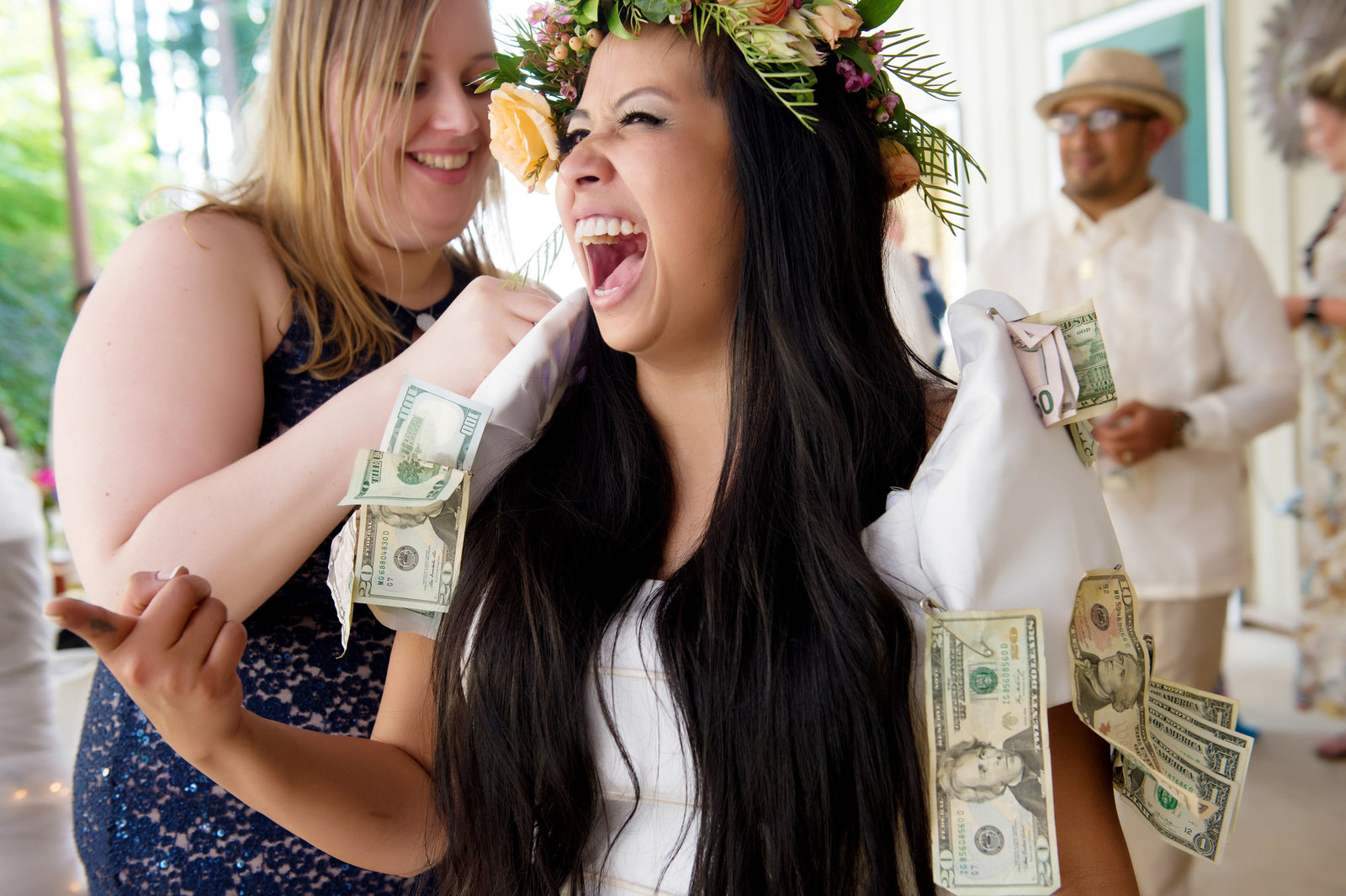 bride laughs as she has money pinned to her dress
