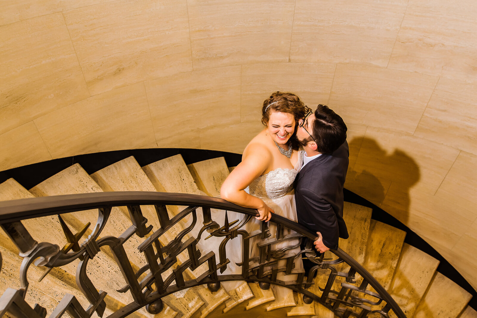 Candid wedding photo of bride and groom cuddling in a stairwell at The Chase Park Plaza in St. Louis