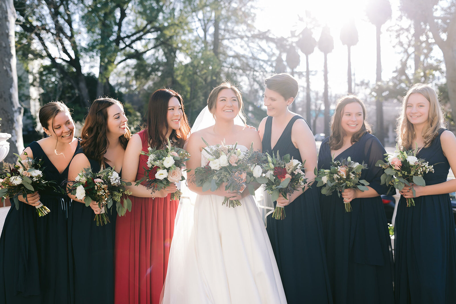 A bride and her bridesmaids giggling outside of the Pavilion before the ceremony is to begin.