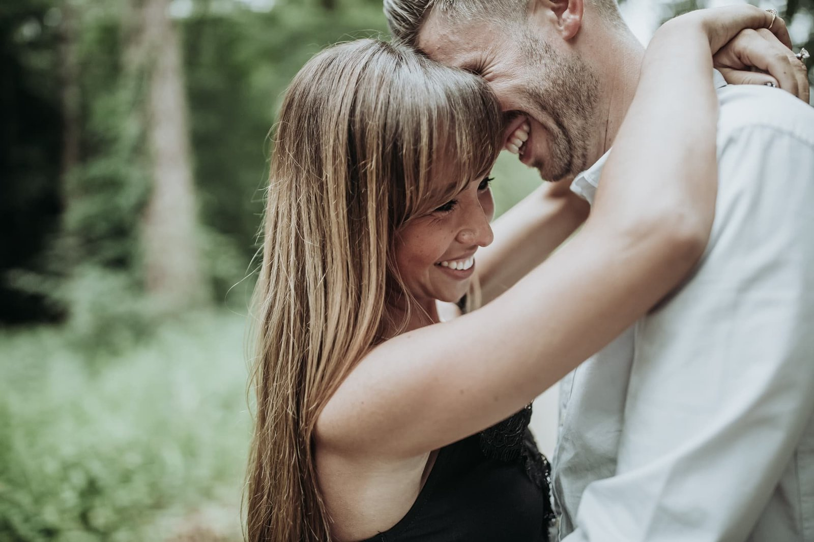 Engaged couple enjoy a hug in Bacton wood, Norfolk and laugh.