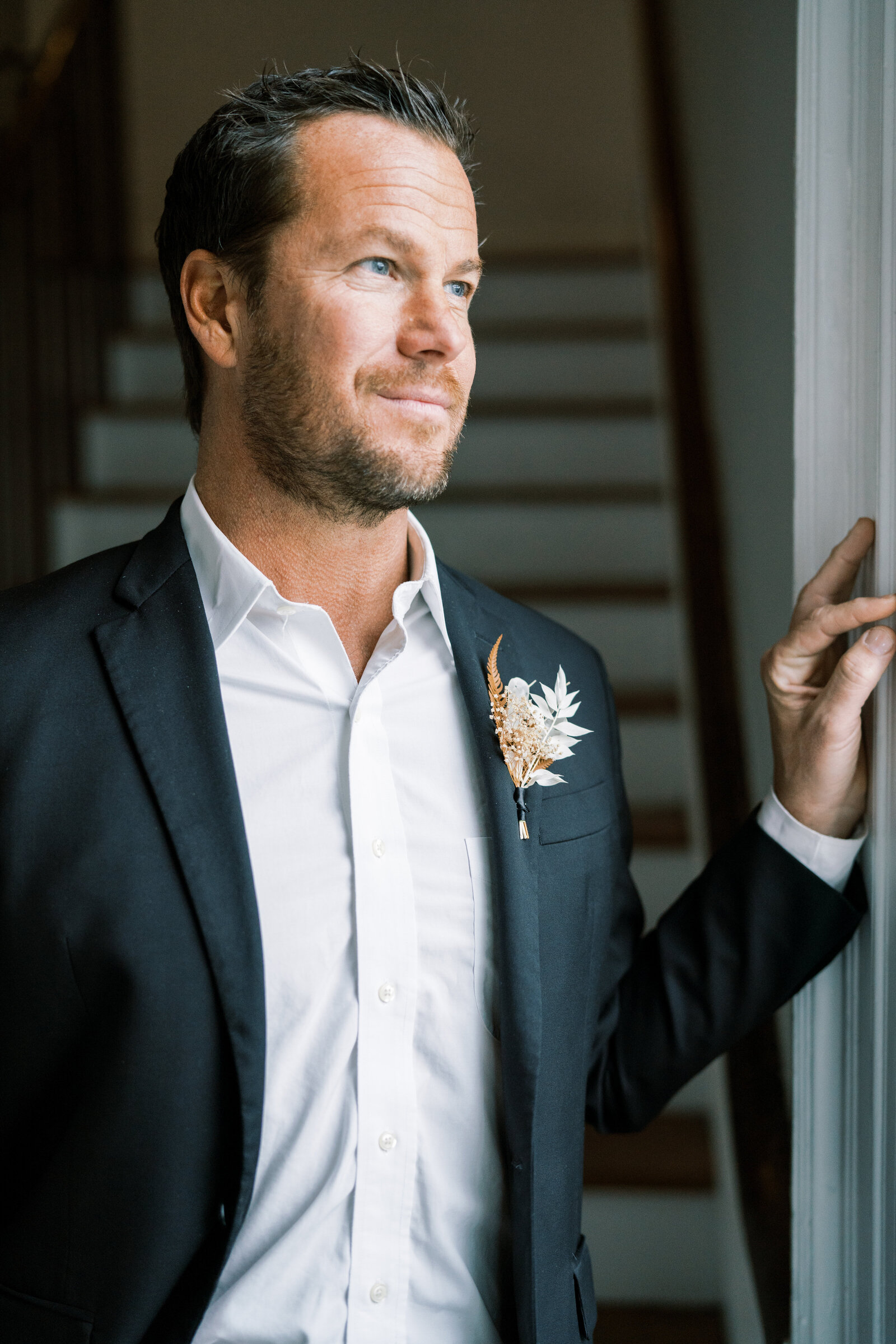 groom in a black suit looking out the window