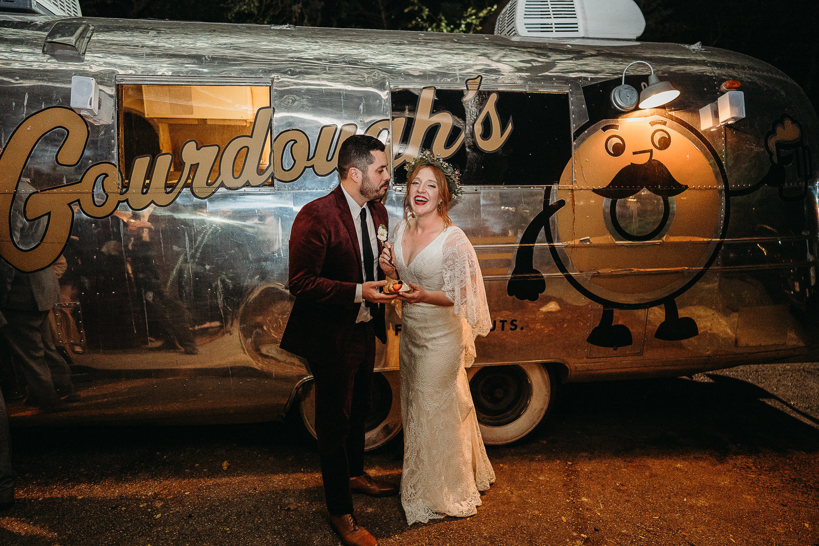 couple shares a donut outside food truck after wedding