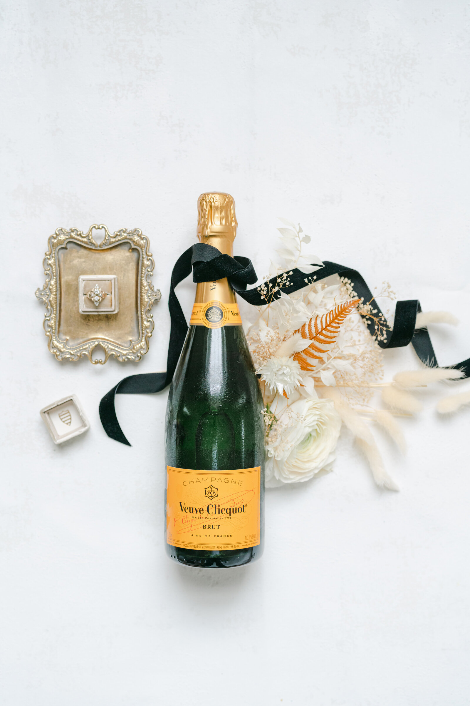 champagne bottle with flowers and wedding ring