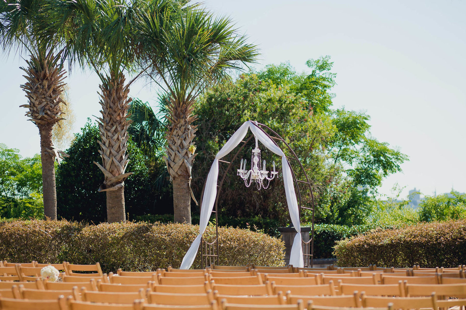 Chandelier hangs at altar by palmetto trees, Harborside East, Mt Pleasant, South Carolina