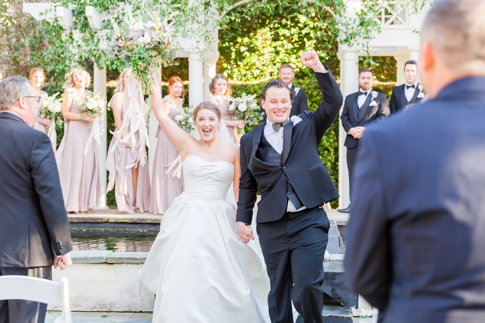 bride and groom share a cheer together while walking down the aisle after just being married at the william aiken house
