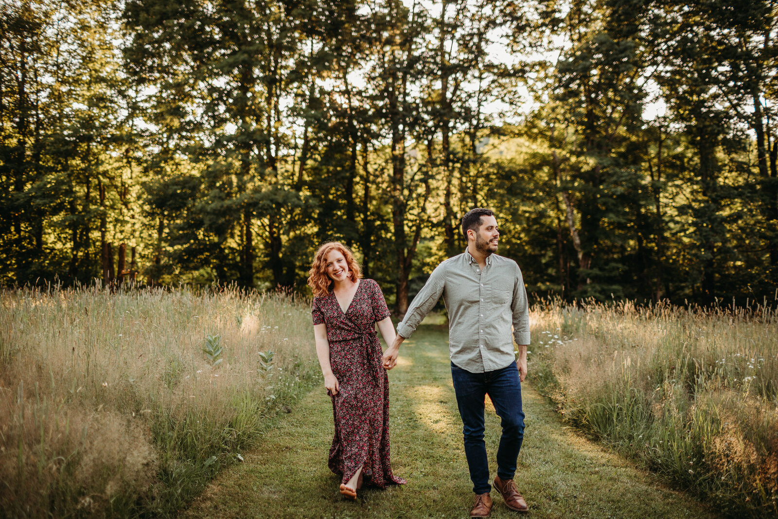 couple walks holding hands in a field during engagement shoot