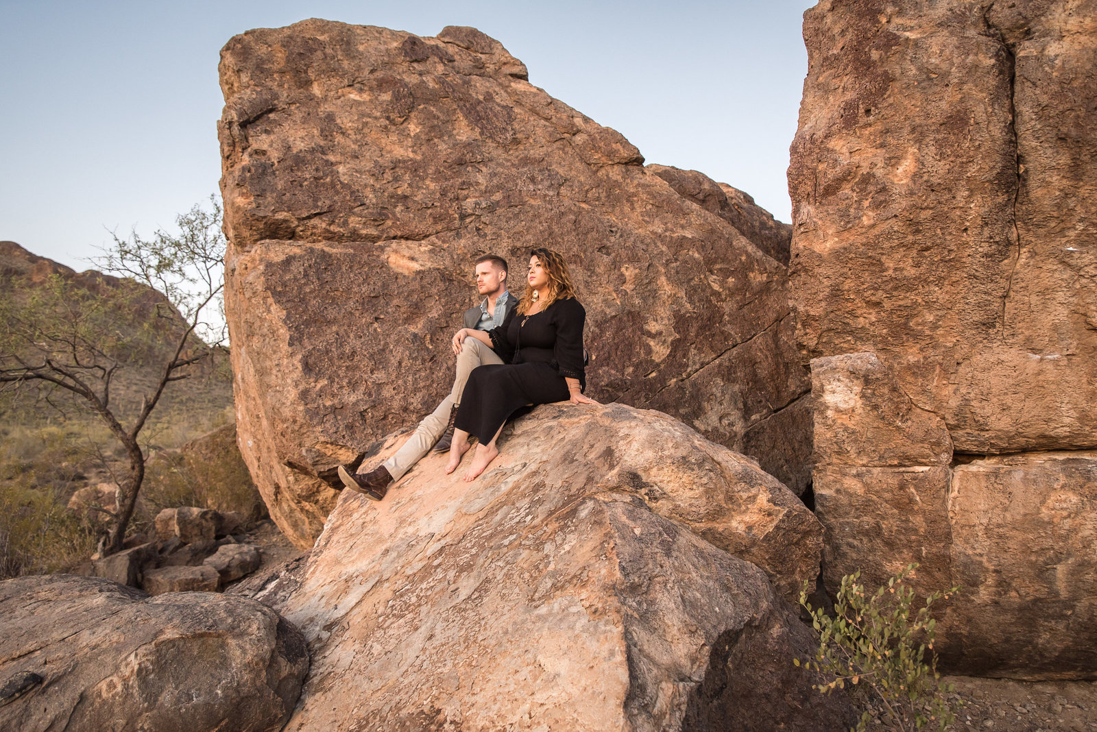Tucson Gates Pass Desert Engagement Session Photo of Engaged Couple Sitting on Red Rocks | Tucson Wedding Photographer | West End Photography
