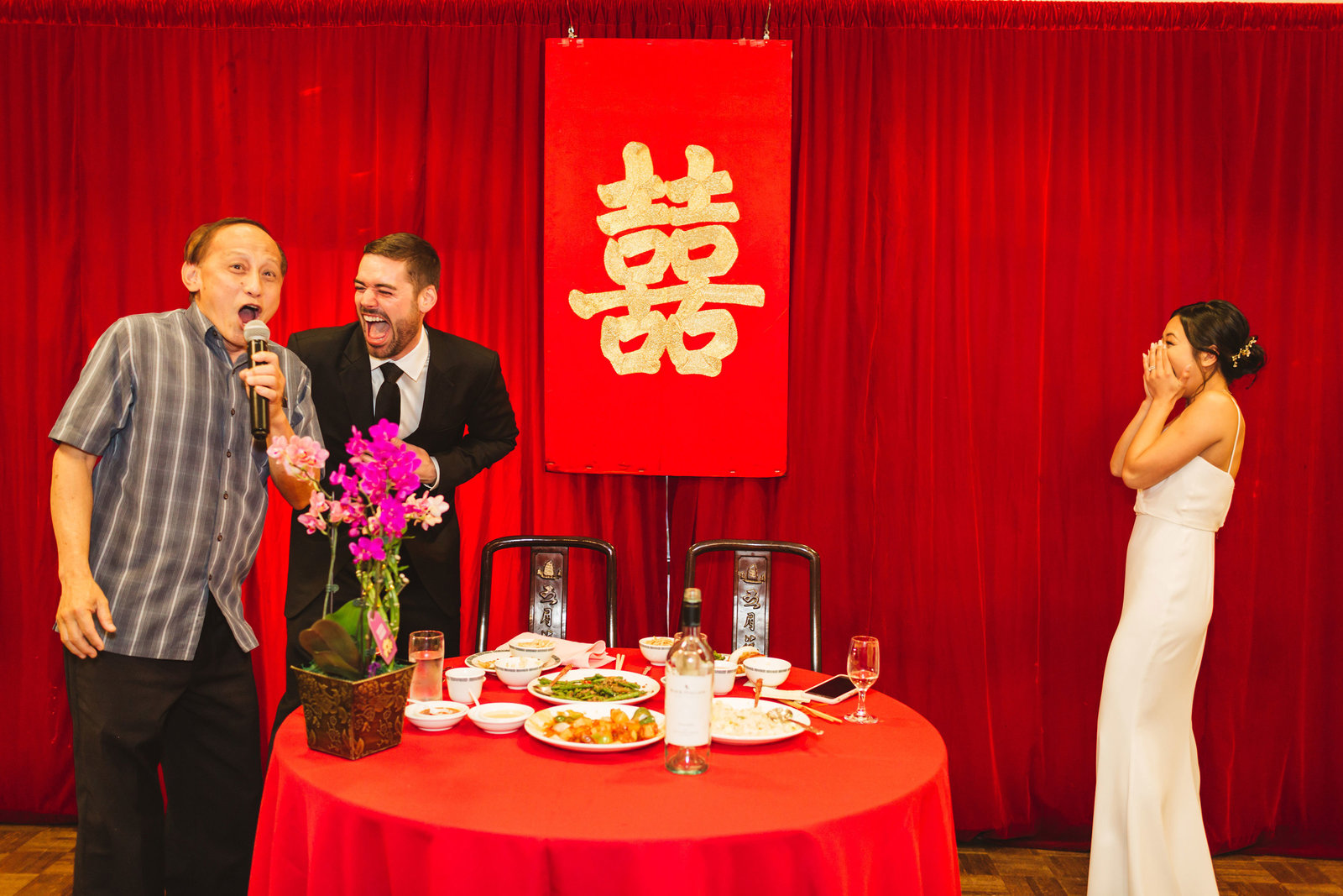 candid moment at chinese banquet wedding while uncle takes the mic