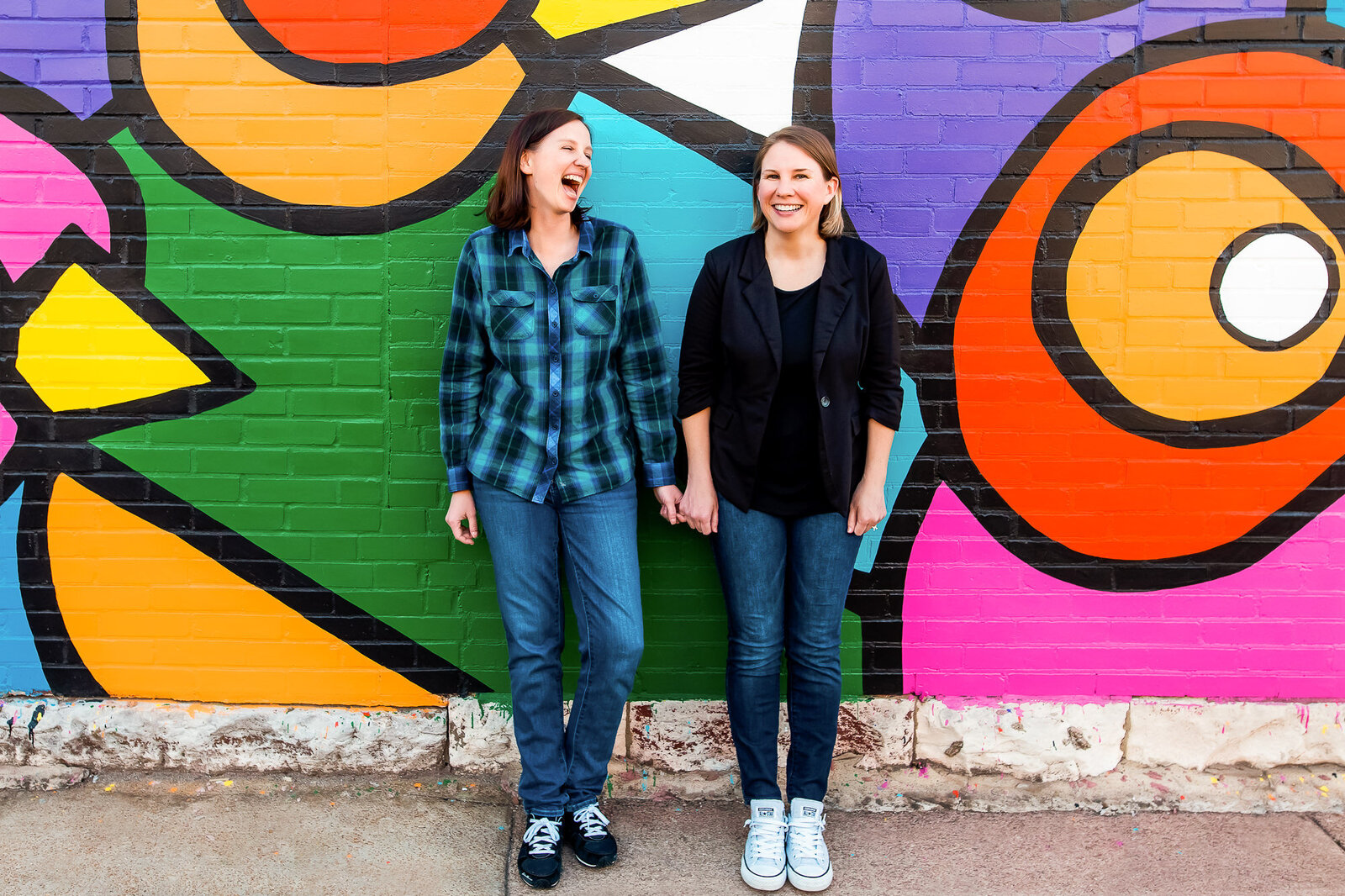 LGBT engagement photo session with a lesbian couple in front of a colorful mural The Grove in St. Loui