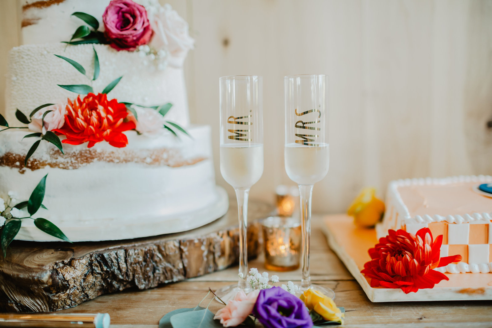 Mr and Mrs champagne flutes in front of cakes at Allenbrooke Farms