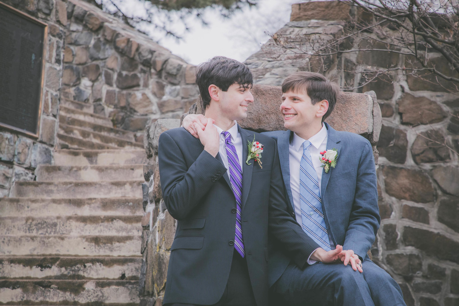 Two grooms get close during their park elopement.