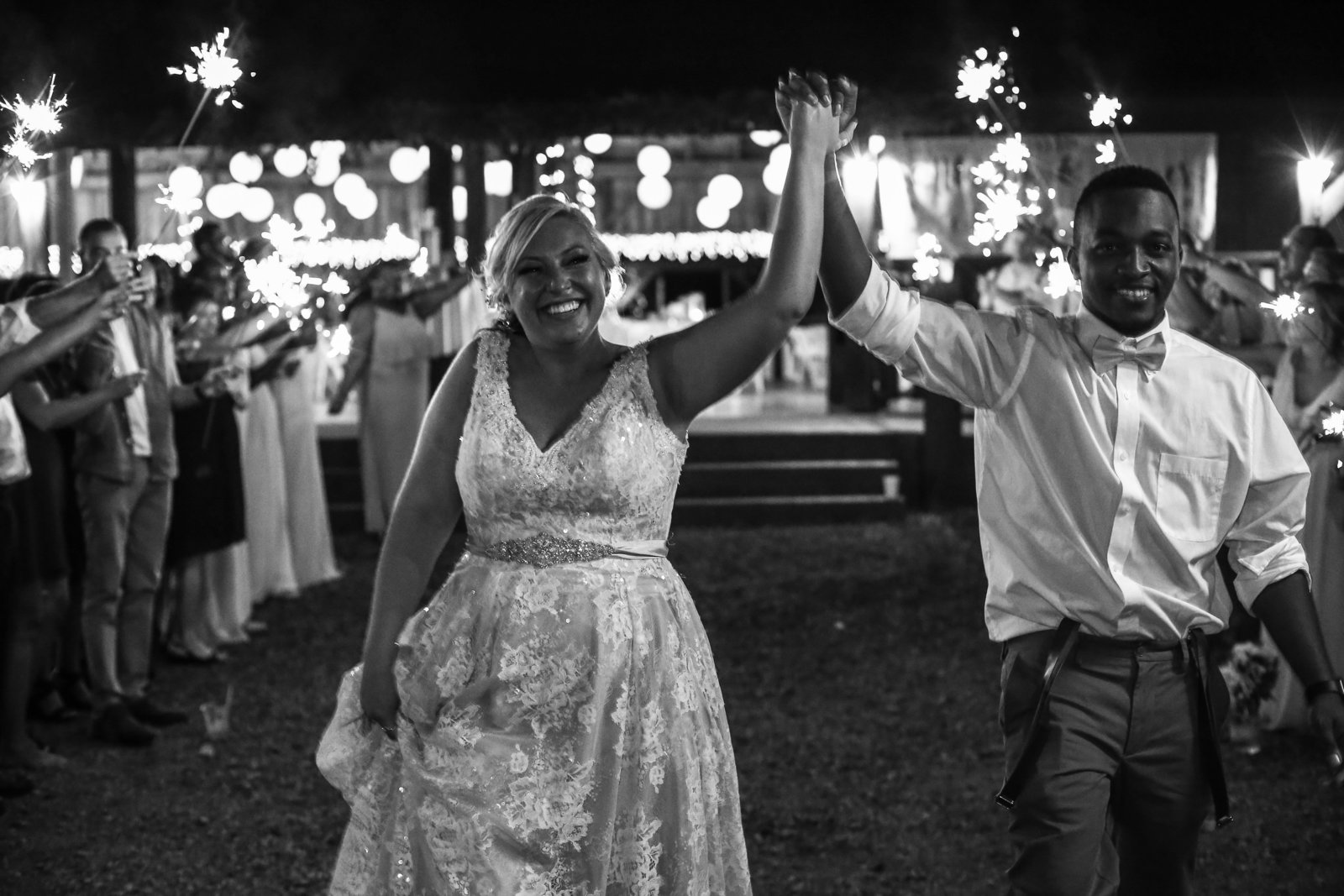 Guests hold sparklers as bride and groom leave Betsy's Barn wedding