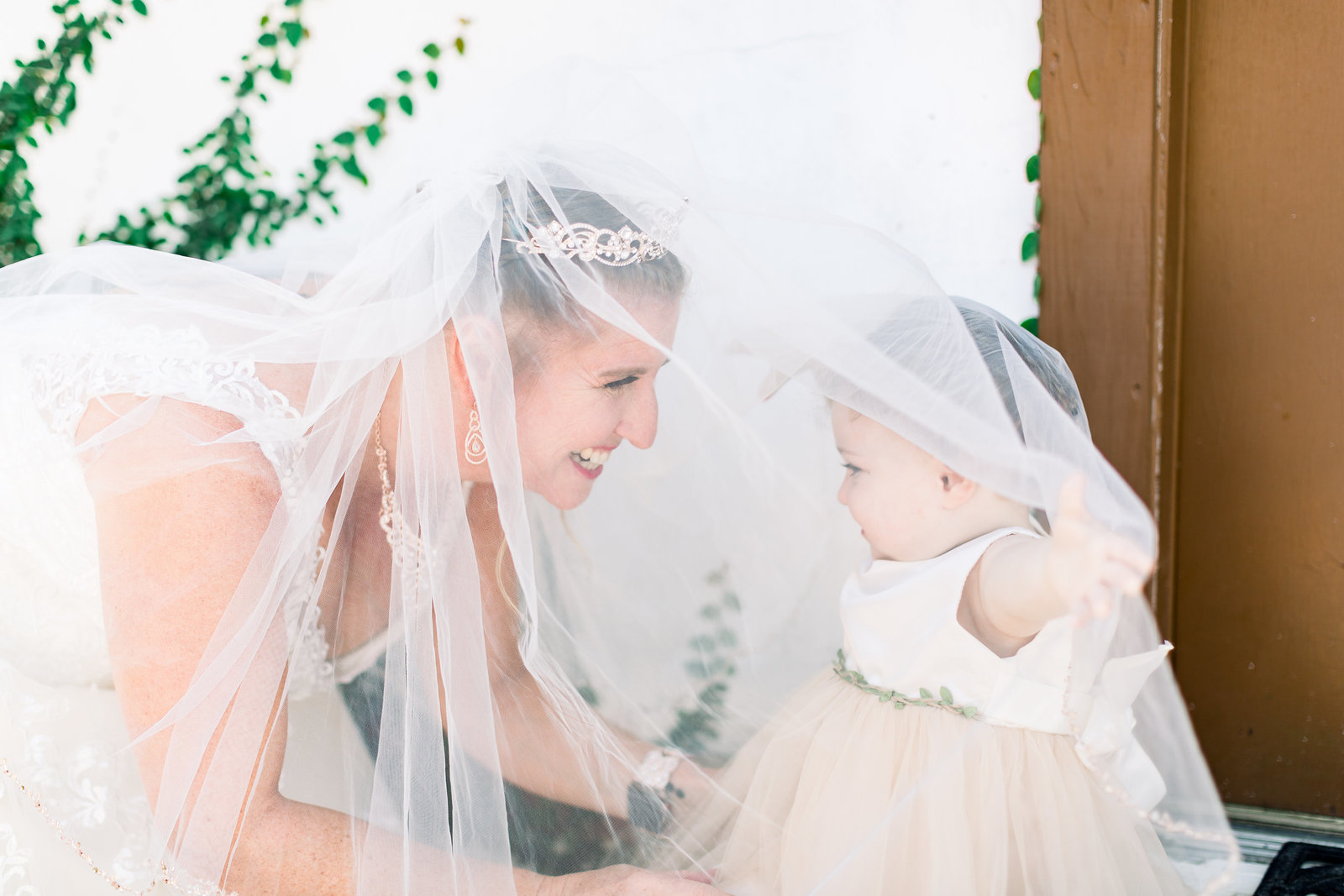 bride smiling and playing her veil with the flower girl