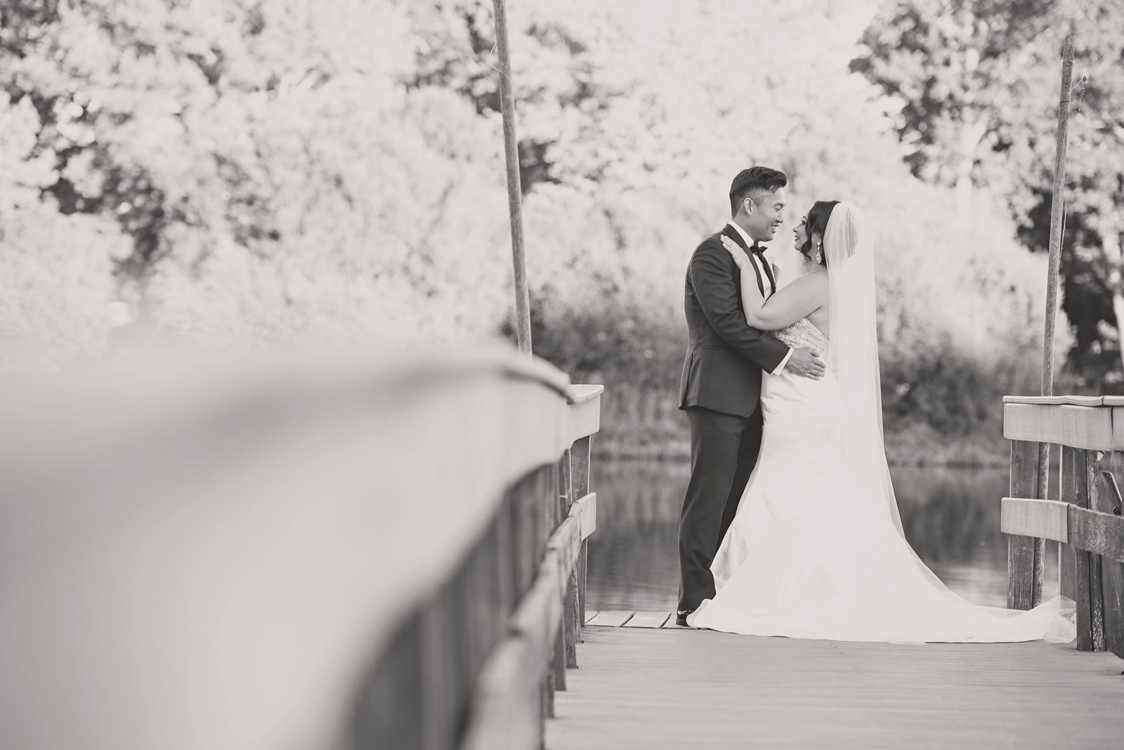 Bride and groom smiling on bridge at Camp Pa-Qua-Tuck