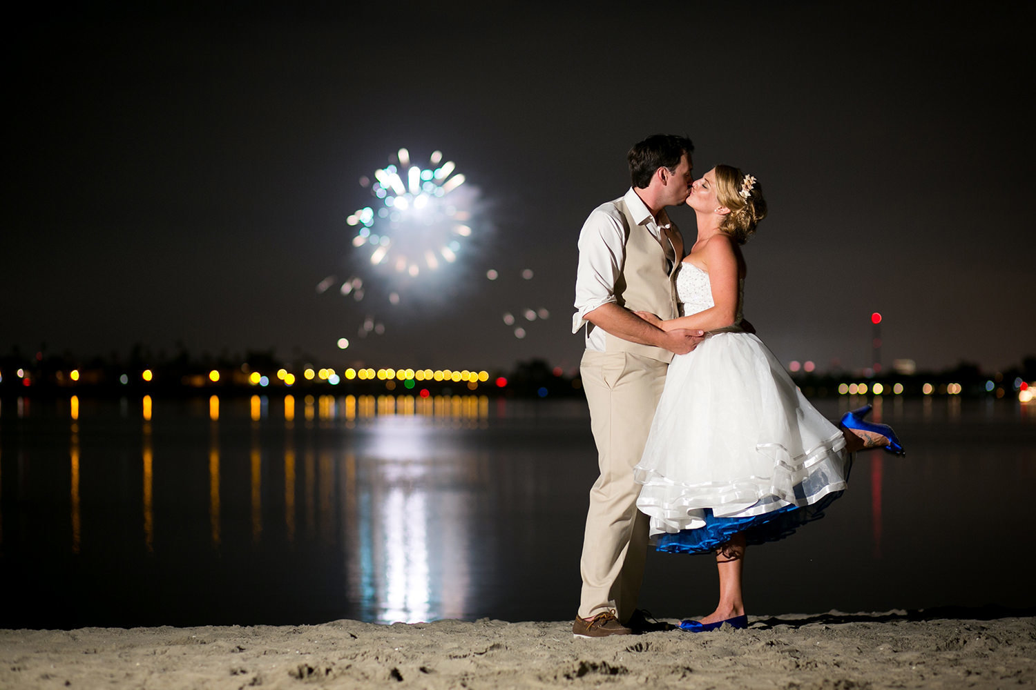 bride and groom with fireworks in background