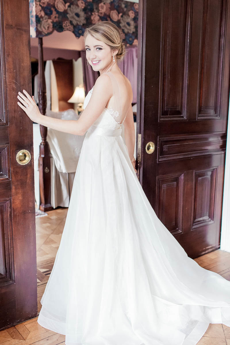 Bride stands by wooden sliding doors, John Rutledge House Inn, Charleston, South Carolina. Kate Timbers Photography.