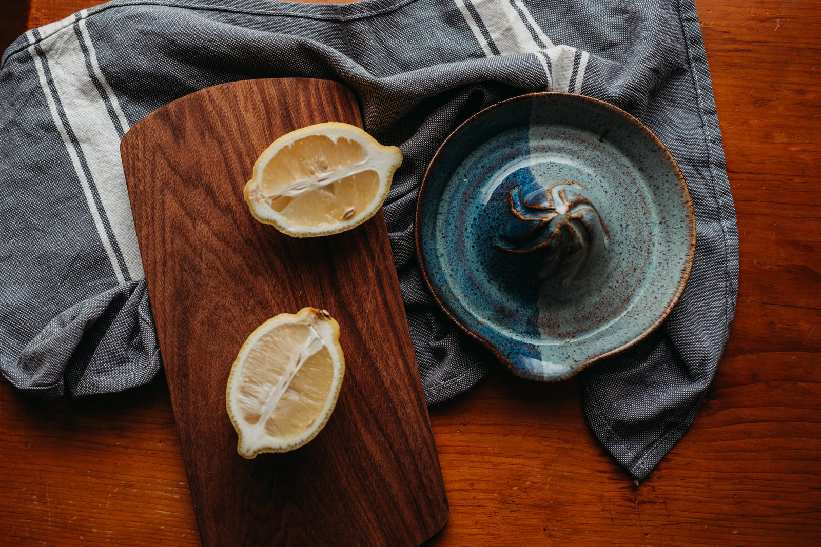 overhead shot of pottery citrus juicer next to lemons and a towel
