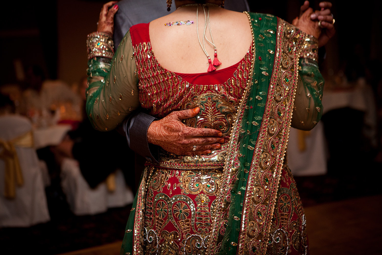 Romantic closeup of bride's sari and grooms hand during their first dance