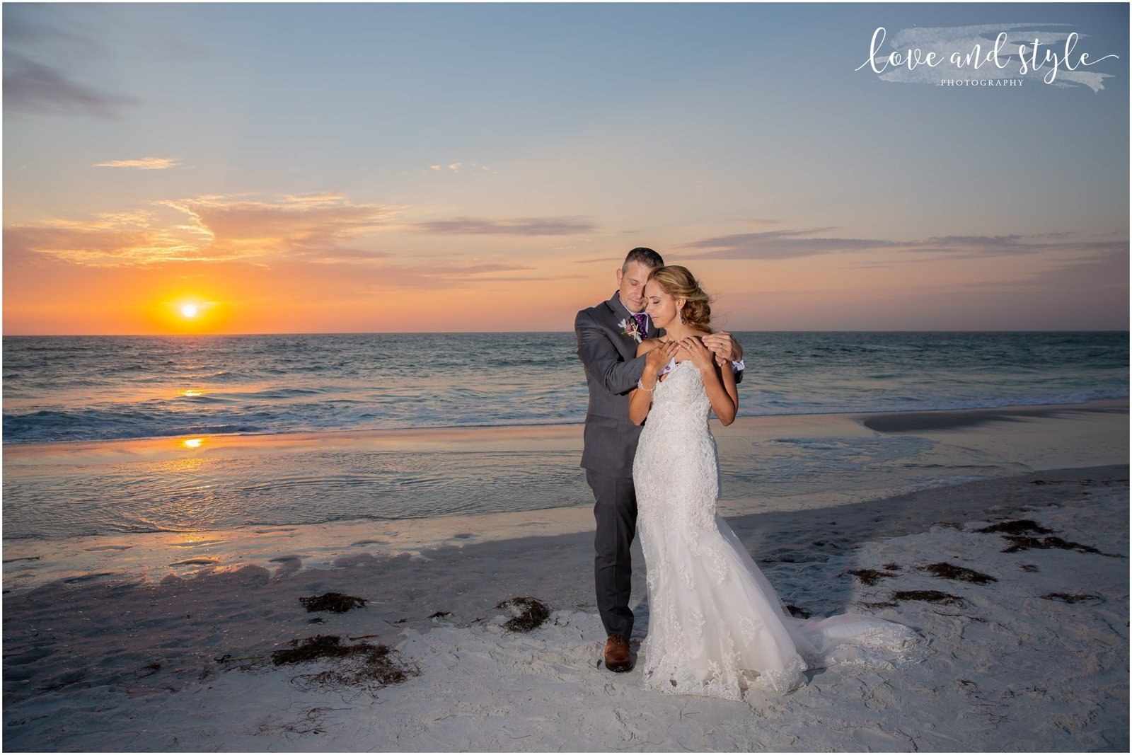 Bride and groom hugging at sunset on Bradenton Beach in front of The Beach House Restaurant