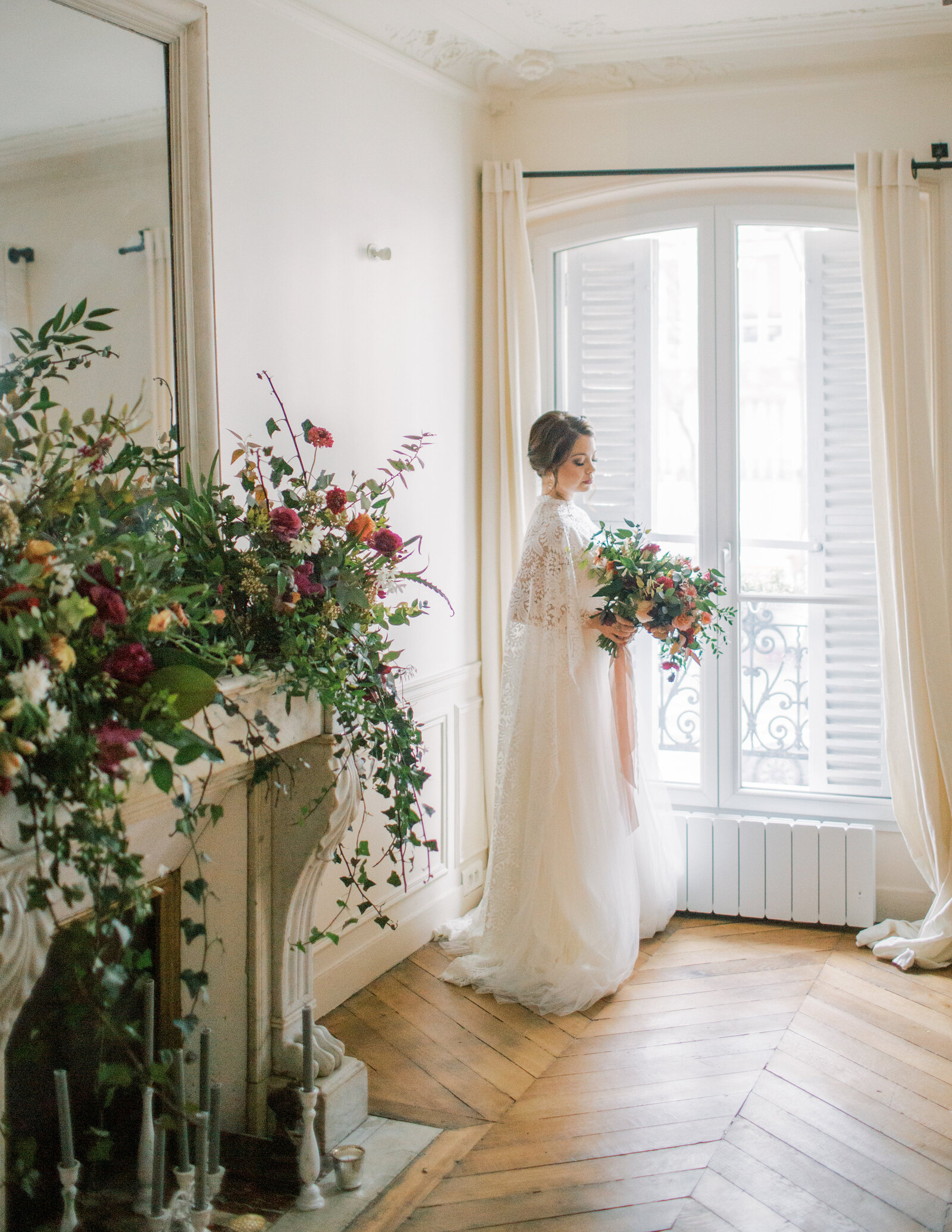bride holding a bouquet and looking out the window in Paris apartment