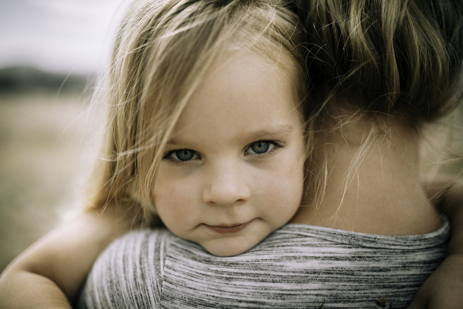 Little girl over mums shoulder up close intimate photo with big blue eyes and blonde hair. Melbourne Family Photography session with Sapphire and Stone Photography