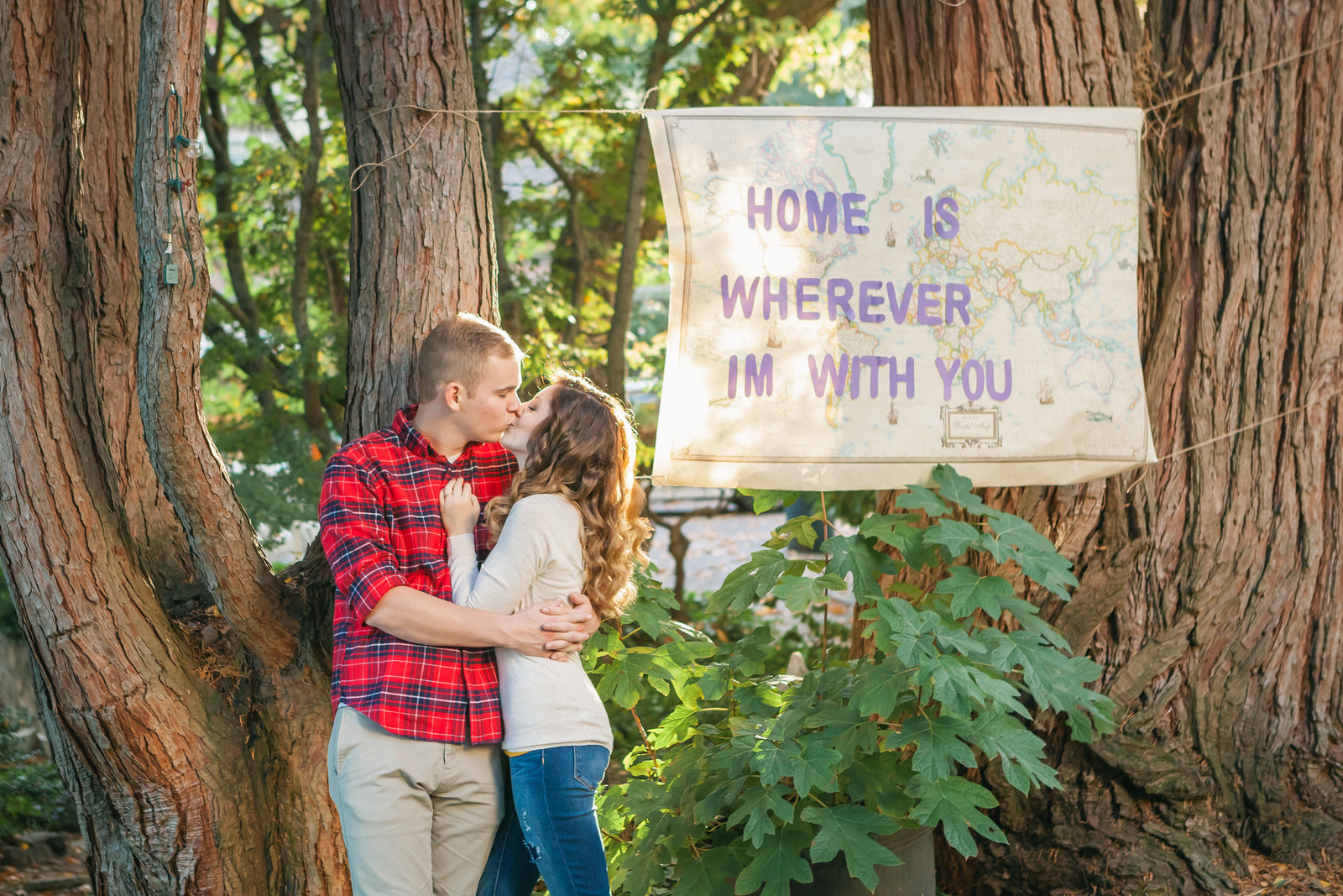 Auburn engaged couple with a sign under trees