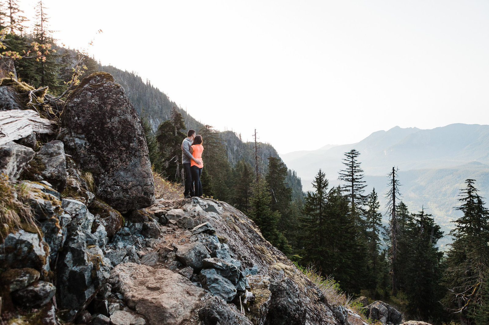 A couple gazes out at the valley below from a backcountry trail during their adventure engagement session with adventurous elopement photographer amy galbraith