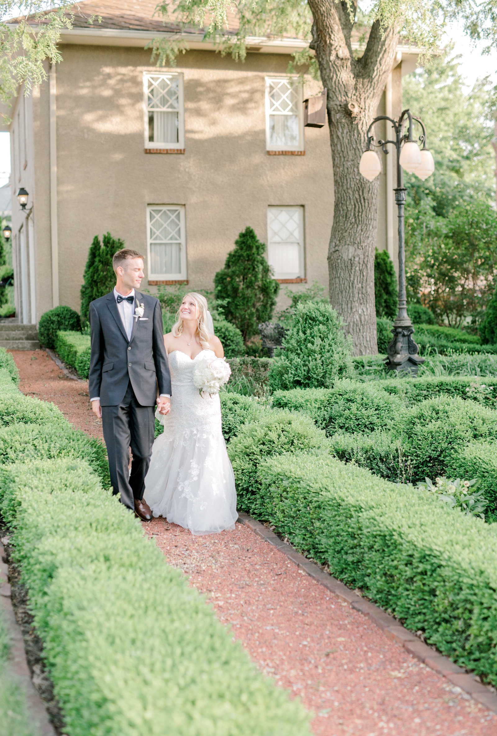 bride and groom walk through a romantic garden in Perry, Iowa