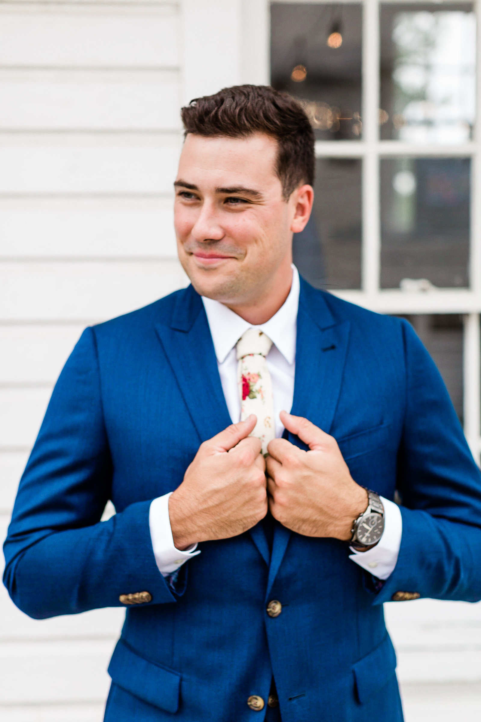 •	Close up of handsome groom in blue suit with white floral tie