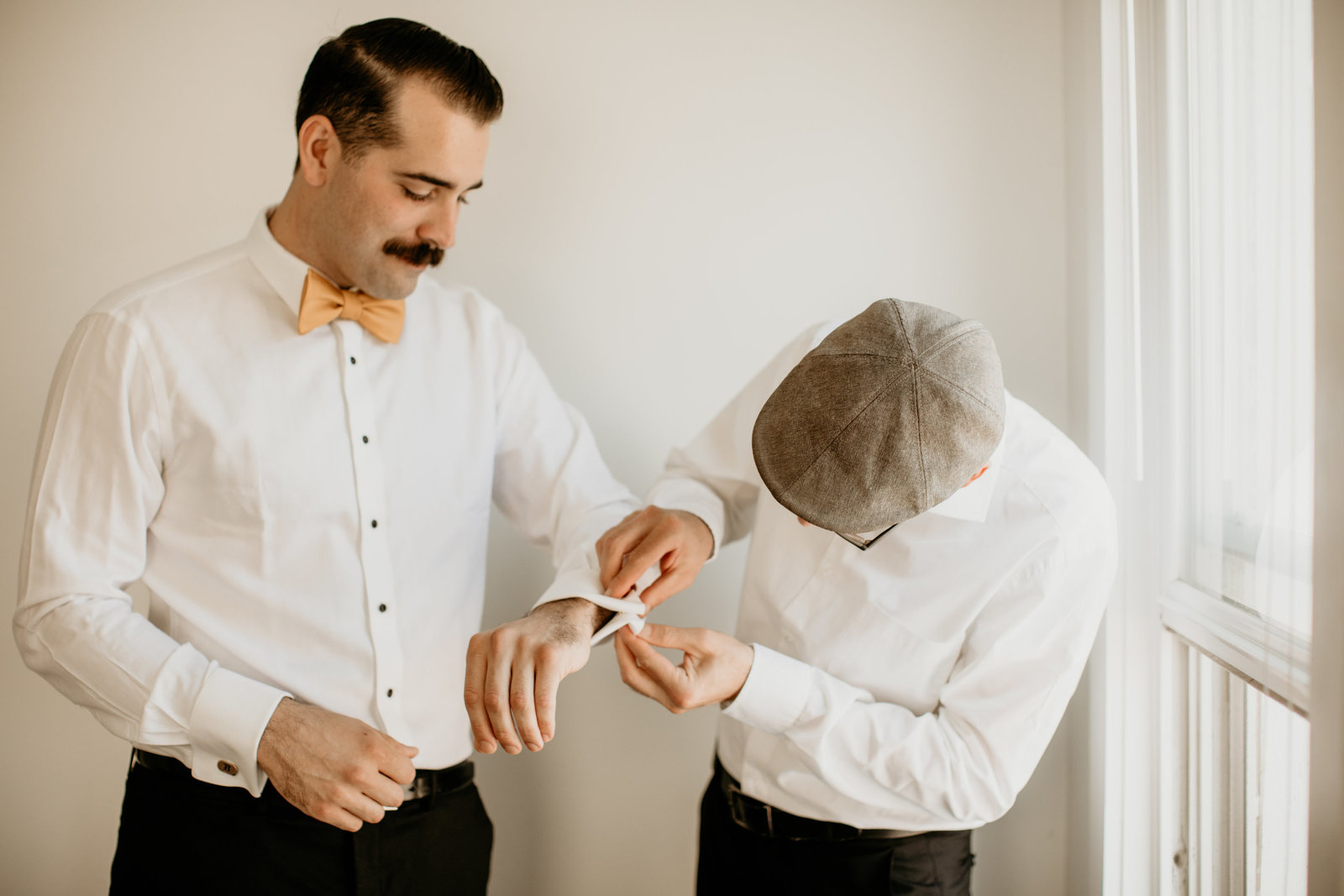 groomsmen helps groom with his cufflinks.