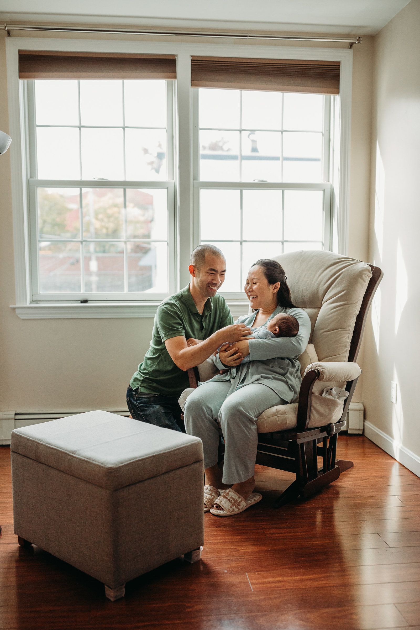 couple with newborn baby sit in neutral rocking chair during newborn photos in south boston
