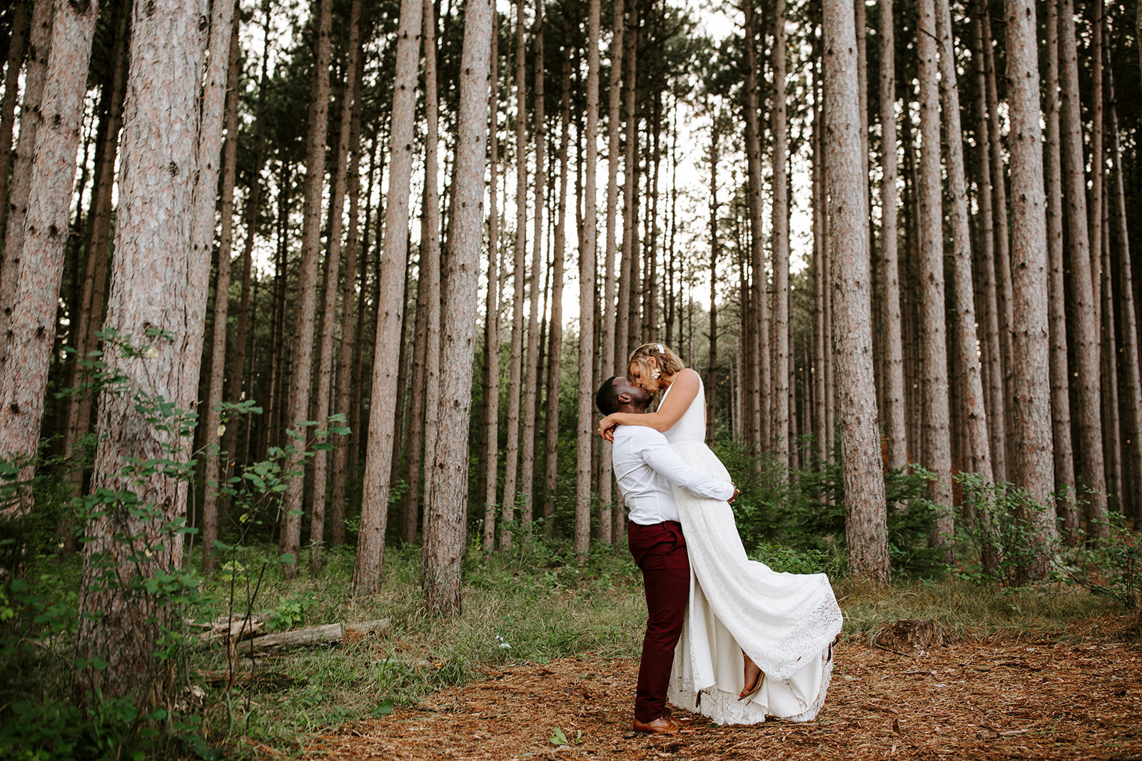 Groom lifting his bride kissing in tall pine tree at Pinewood Wedding Venue