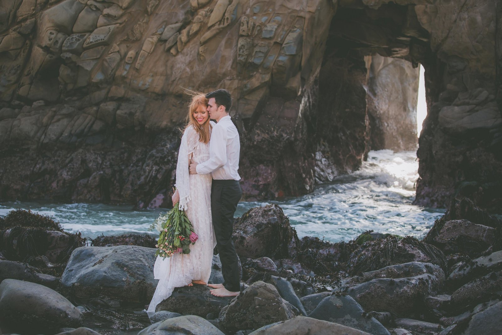 A bride and groom balance on rocks in Pfeiffer beach.