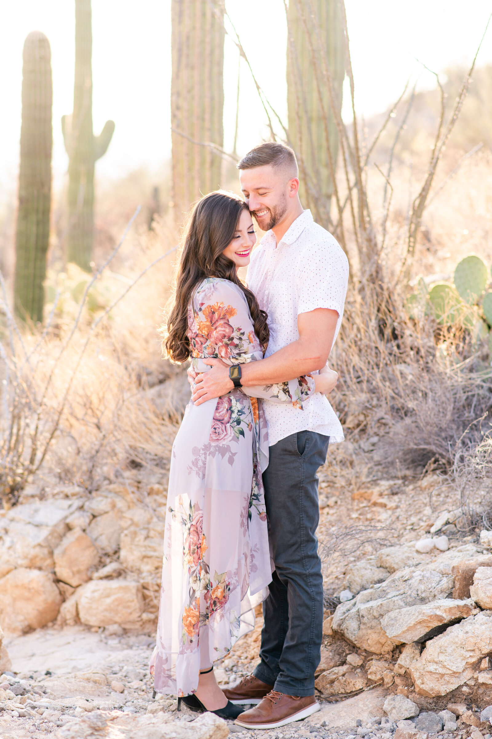 engaged couple surrounded by cacti in Tucson desert mountainside