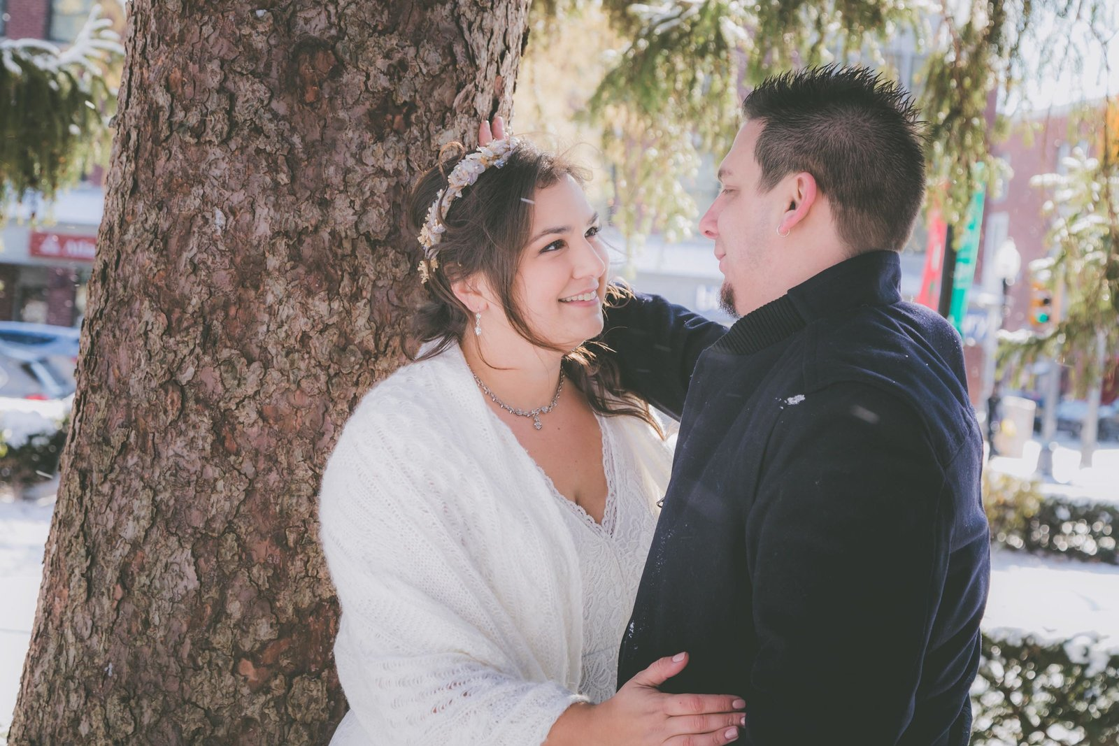 Groom looks at bride against the tree while it flurries on their elopement day.