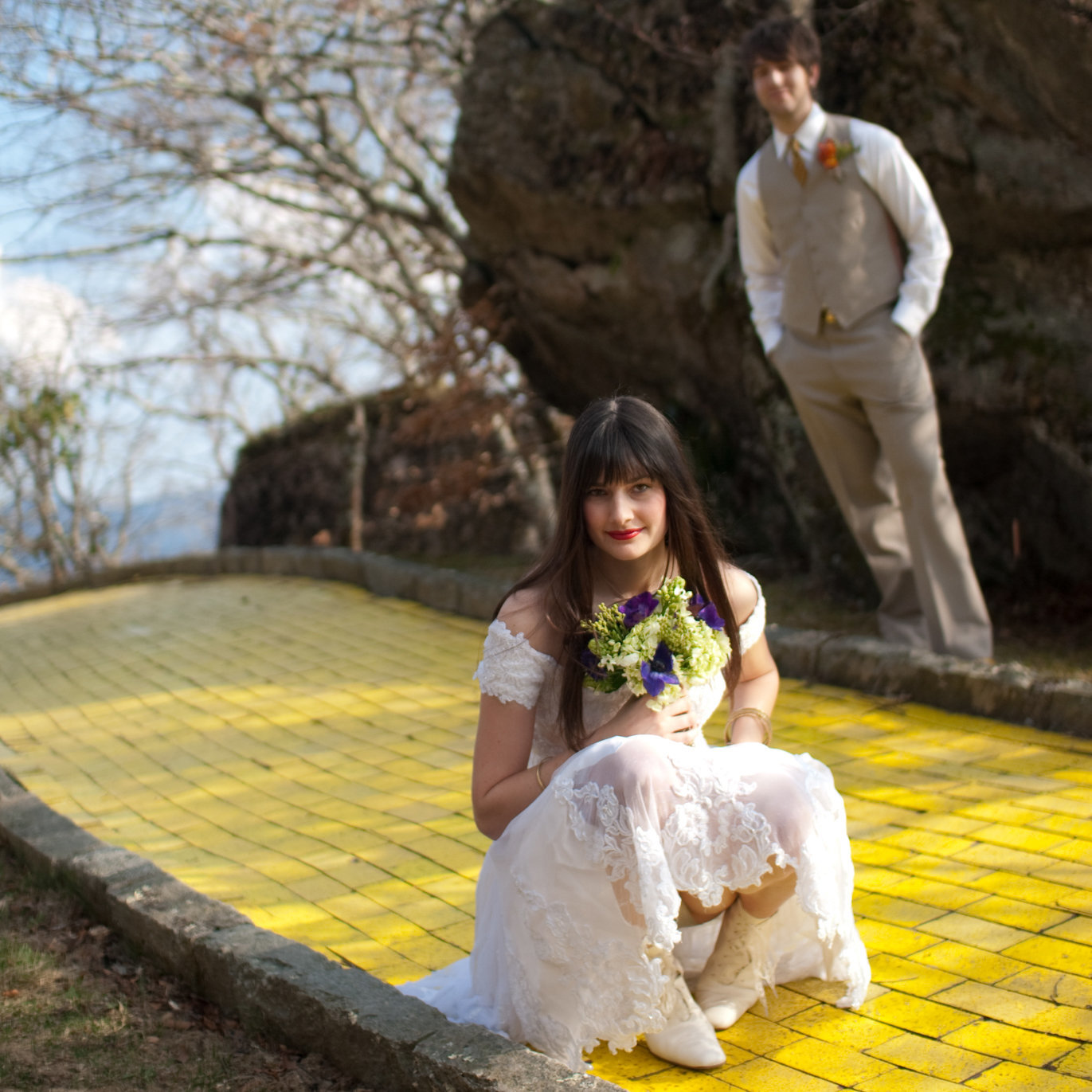 a pretty bride kneels down on the yellow brick road in front of a groom at land of oz