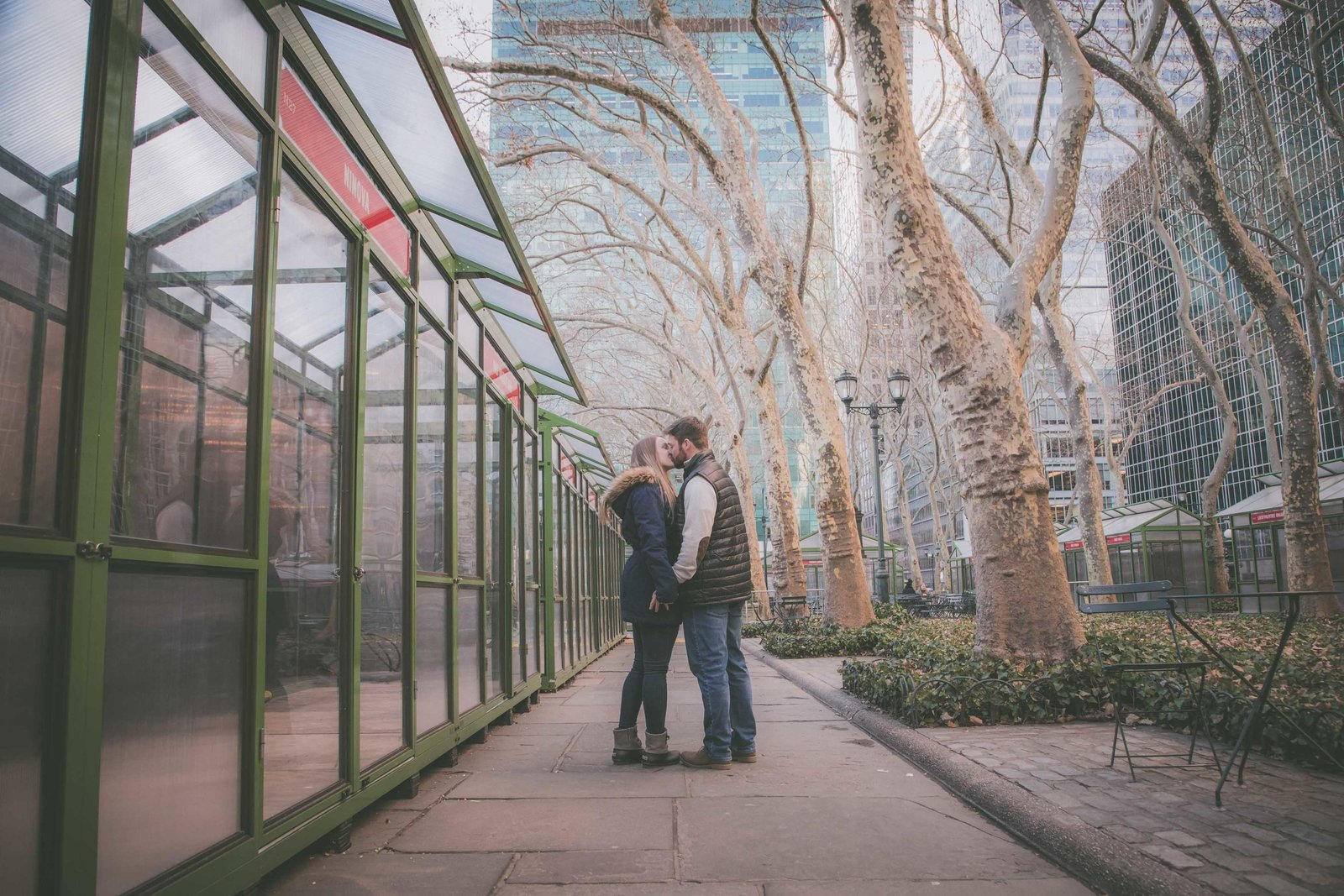 Wide angle of couple kissing in Bryant Park after proposal.