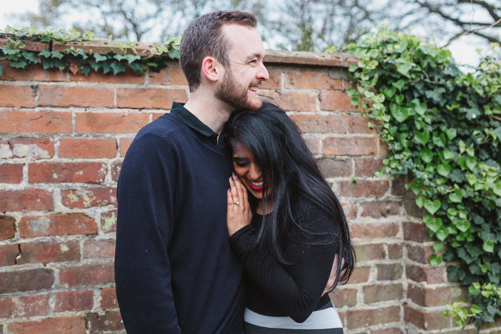 Cuddling engaged couple lean against red brick wall for a natural couples photo