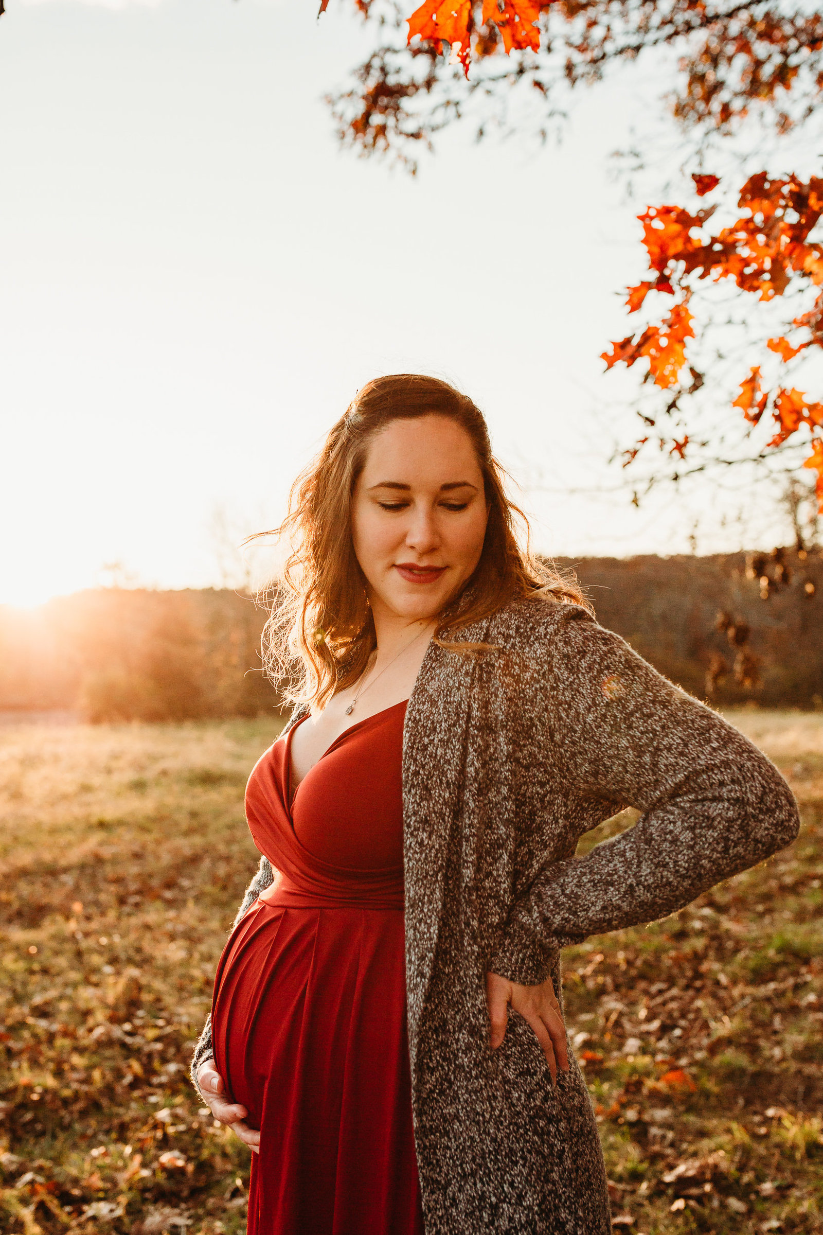 pregnant woman in red dress at autumn sunset