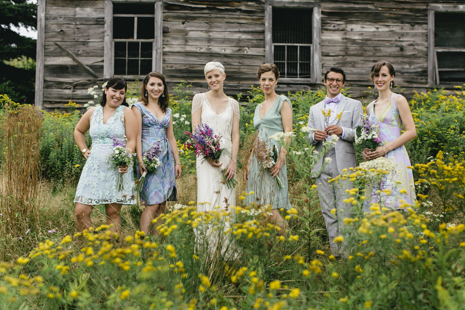 bridesmaids in yellow flower field barn