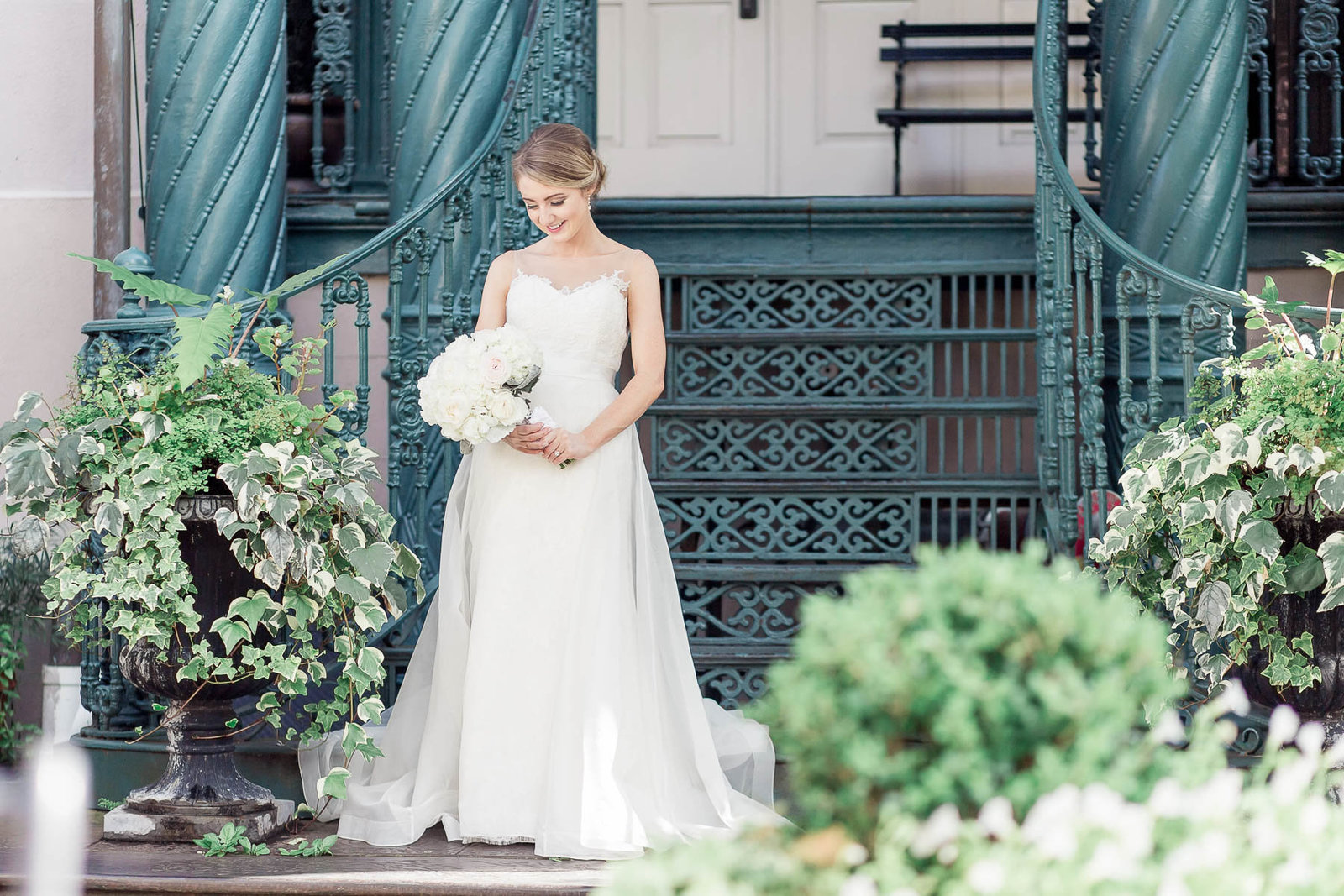 Bride poses on ornate staircase, John Rutledge House Inn, Charleston Wedding Photography.